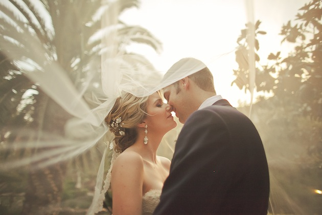Bride and groom kissing under veil